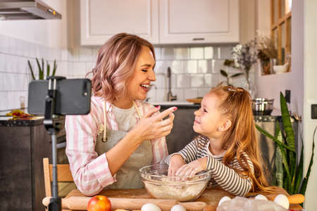 food bloggers mother and daughter are kneading dough and smiling while preparing it for baking, in light kitchen at home