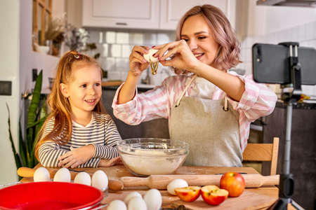 food blogger mother and child daughter are going to cook, bake cookies or pie at home, tasty food for while family, woman and child girl have fun and talk, enjoy the process