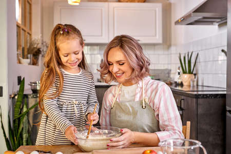 mother and pretty daughter cooking together, enjoy process and communication. woman teach her daughter kneading dough for domestic cookies