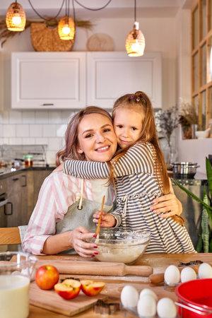 daughter hugging mother while cooking, caucasian family preparing dough, bake cookies, look at camera smiling