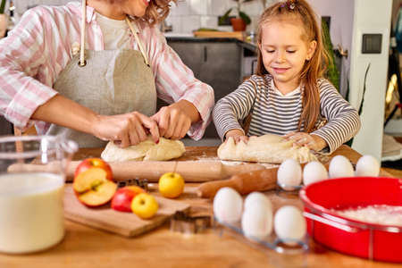 child girl knead with mom in the kitchen, going to bake delicious cookies. family at home at weekend, mother teach child girl to cook