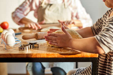 mother and daughter kneading dough for homemade dessert in kitchen, teach and learn