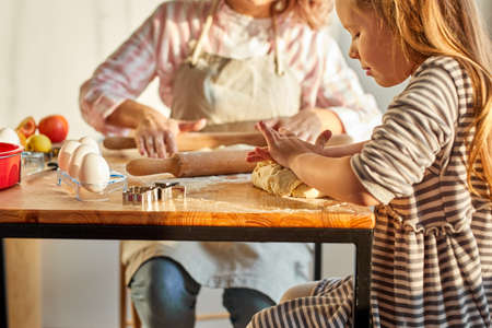 caucasian family child with mother rolling out the dough using rolling pin in light room, modern kitchen at home. adult woman teach the girl