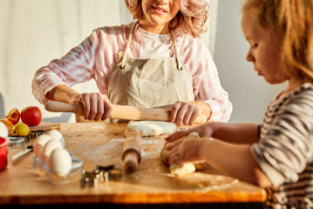 woman and child girl cooking together in kitchen, young mom teaches cute kid girl kneading dough for domestic pie preparing surprise for family Archivio Fotografico