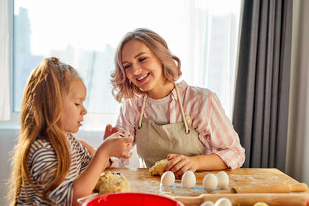 little girl and her mom in apron kneading the dough in kitchen,homemade pastry for bread, pizza or bake cookies. family fun and cooking concept