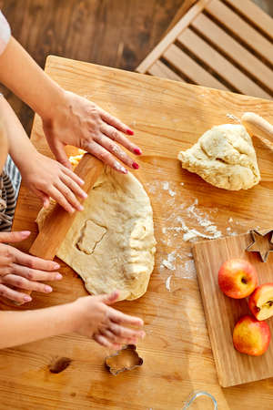 cropped mother teaches daughter prepare dough in the kitchen with fun, close-up photo of hands, top view