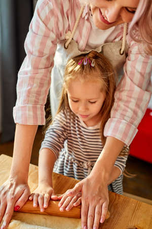 mom showing daughter how to roll out dough for pie or cookies, little cute kid child learning muffins bans cooking process with happy mom in light kitchen Archivio Fotografico