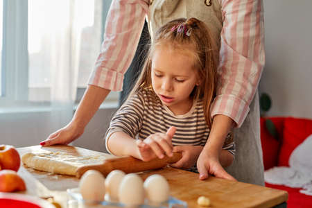 mother showing daughter how to roll out dough for pie or cookies, little cute kid child learning muffins bans cooking process with happy mom in light kitchen