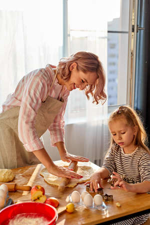 mother is teaching daughter to roll out dough for baking cookies, in the kitchen at home. on table Archivio Fotografico