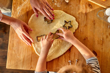 woman and girl hands cutting dough with cookie cutters on kitchen table, daughter is helping mpm to make cookies on kitchen, top view