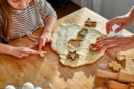 girl baking cookies with mother, help to roll out the dough using moulds to make the cookie cuttings Archivio Fotografico