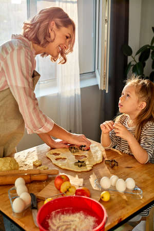 mother and daughter prepare flour baked goods on a table in the kitchen at home, young adult woman and kid girl enjoying time together while cooking. Happy mothers day concept. Archivio Fotografico