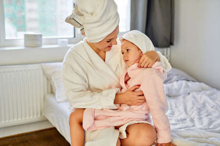 woman in bathrobe and towel enjoy time on bed with daughter little girl, mother hugs her child, smile Archivio Fotografico