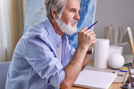 painter man painting for hobby, he sits thinking, in contemplation, at home Archivio Fotografico