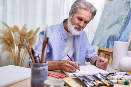 painter is drawing at home in light room, gray bearded man is creating a masterpiece using a pencil Archivio Fotografico