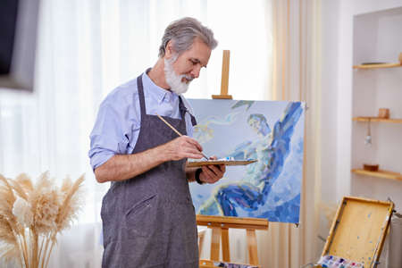 senior artist painting on easel, canvas, intelligent professional painter enjoys art