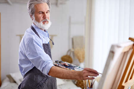 artist holding creating masterpiece using paintbrush, stand near canvas, gray haired male in apron enjoy drawing Archivio Fotografico