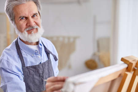 senior artist man with wrinkles looking at camea during work on canvas, in art studio Archivio Fotografico