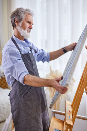 artist man looking at canvas his masterpiece, stand thinking, in contemplation, enjoy drawing, painting Archivio Fotografico