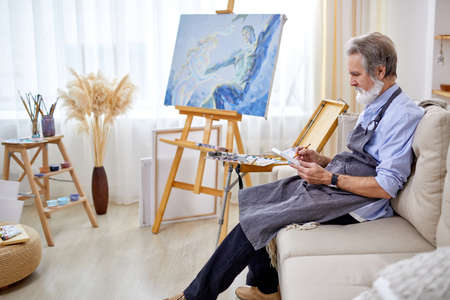 painter man sitting on sofa, concentrated on work with pencil, sit looking at sheet, in light art studio