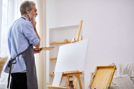 thoughtful artist man standing behind canvas on easel, in contemplation, think what to draw Archivio Fotografico