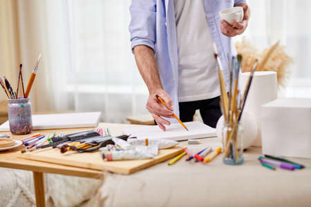 close-up photo of artist man drawing with pencil on sheet, other different tools for painting on table
