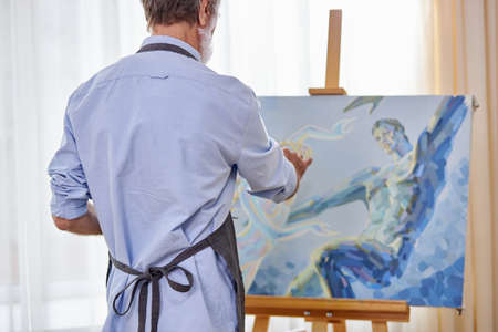 artist in apron during work, stand opposite the canvas with blue painting