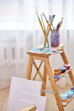 close-up photo of paints, paintbrushes, easel and canvas in light art studio room Archivio Fotografico