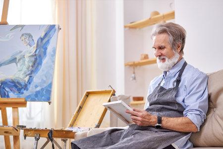 artist sit drawing, smiling, enjoying the work of creating masterpiece. in studio Archivio Fotografico