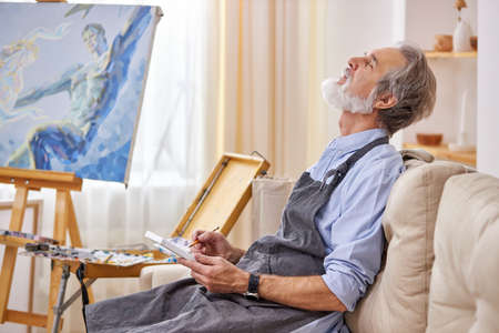 a man artist is waiting for a muse to create a masterpiece, immersed in thought, sit thinking on sofa in art studio