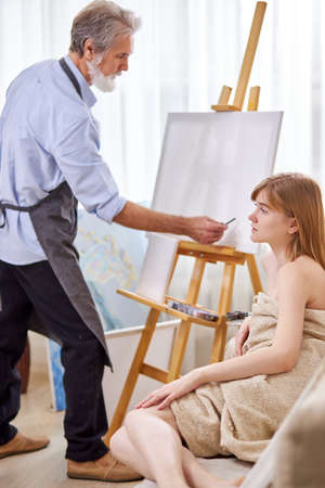 artist drawing portrait of female model on canvas, young caucasian lady sits on couch posing for art Archivio Fotografico