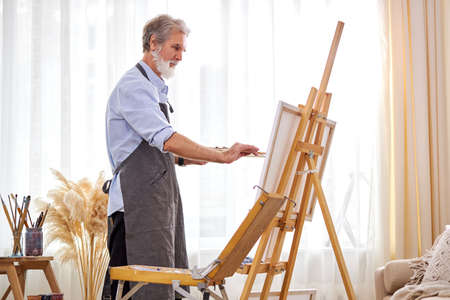 mature artist man concentrated on painting, caucasian male in apron is immersed in the creation of art