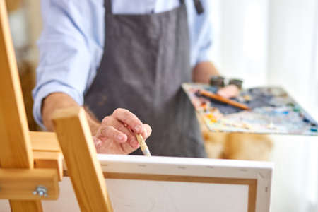 artist applying paint on canvas with paintbrush, his mind full of imagination, creative painter during work. close-up, focus on hands