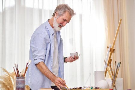 senior artist man draw a sketch on paper and drink tea, enjoy working process in light room studio