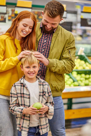 family enjoy shopping with child boy, young parents in supermarket aisle with cute kid boy, in casual wear, smile at camera, have fun