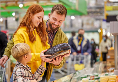 family with son buying fresh vegetables, choose the best one, woman discuss the purchase with husband