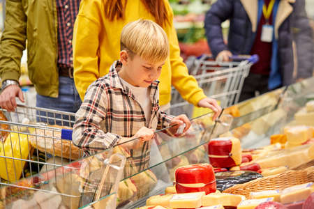 family with son choosing cheese in food store, looking at showcase with products, discussing. shop, food, grocery concept