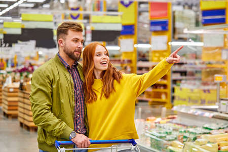 redhead woman show something to husband, in supermarket. young married couple in casual wea in food store Archivio Fotografico