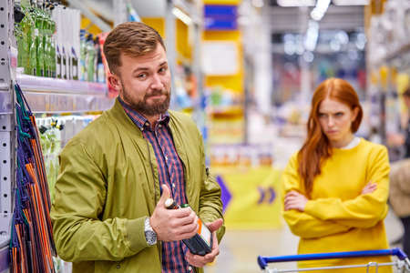 alcoholic man stand with alcohol bottle in hands in supermarket while her offended girlfriend stand in the background, she is dissatisfied with his addiction