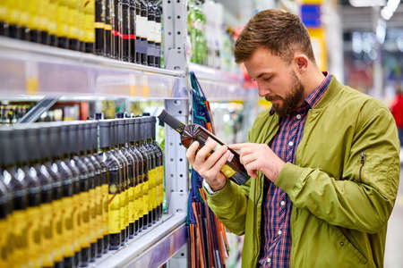 customer male reading wine composition in supermarket, want to buy some alochol for holidays