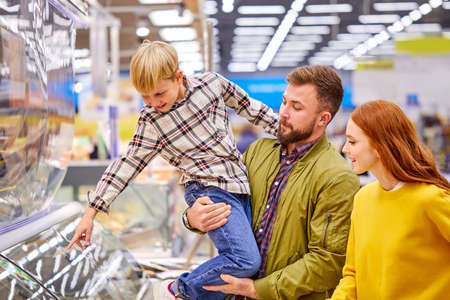 son show something delicious to parents in store, he wants parents to buy it, point finger