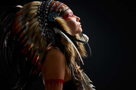 side view on calm indian shaman woman standing with closed eyes, thinking,immersed in hypnosis