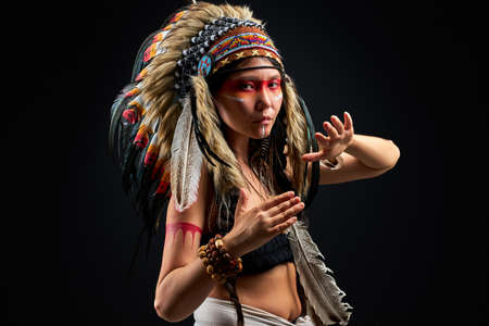 model in indian wearing and colorful makeup posing at camera, with feathers on head. indigenous peoples of the Americas outfit, ethnic woman