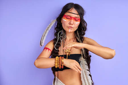 shamanic female with Indian feather on hair and colourful painted make-up, portrait in studio. indian ethnicity 写真素材
