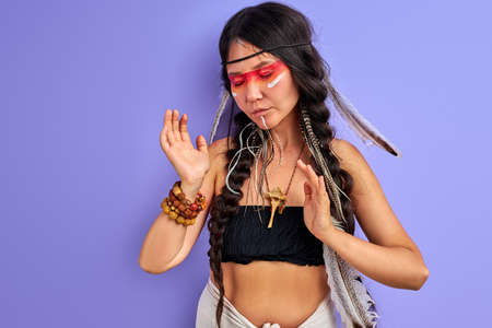 young pagan female is a shaman isolated in studio on purple background, people are different from others. Individuality 写真素材