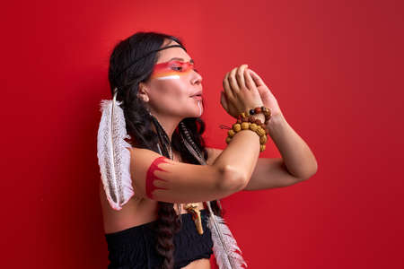 female with art native american creative warrior combat makeup in studio, making rituals. indian woman hunter in traditional ethnic costume with feathers