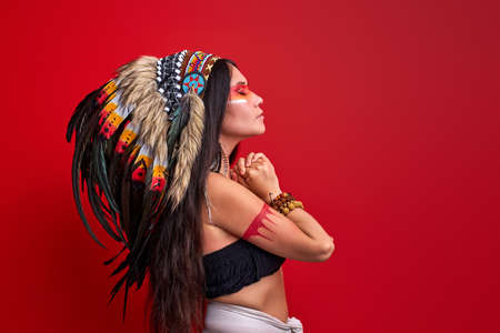side view on long haired shaman woman with feathers on head, indian aborigen costume, stand with eyes closed, isolated on red background. ethnicity, individuality