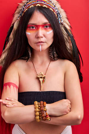 young ethnic lady with roach on her head isolated over red background, female in top posing at camera, shaman