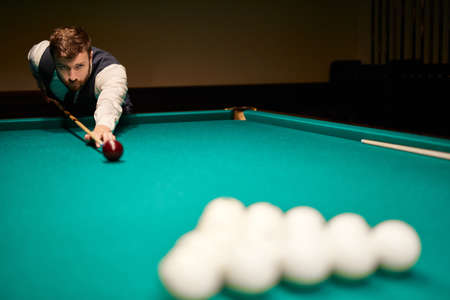 man is playing snooker, he is aiming to shoot the snooker ball. handsome guy holds hands on snooker table. billiards