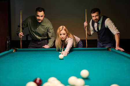 woman receiving advice on shooting pool ball while playing billiards with friends, concentrated on sport game